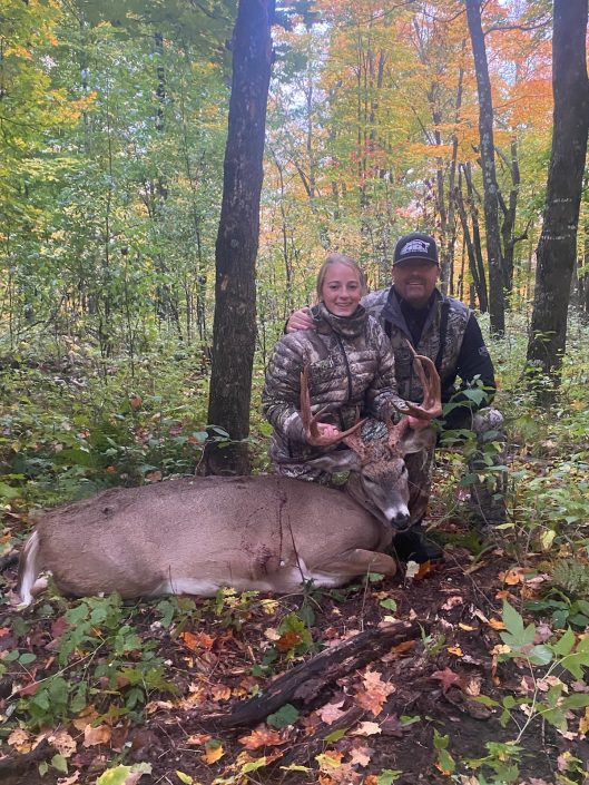 father and daughter with killed deer