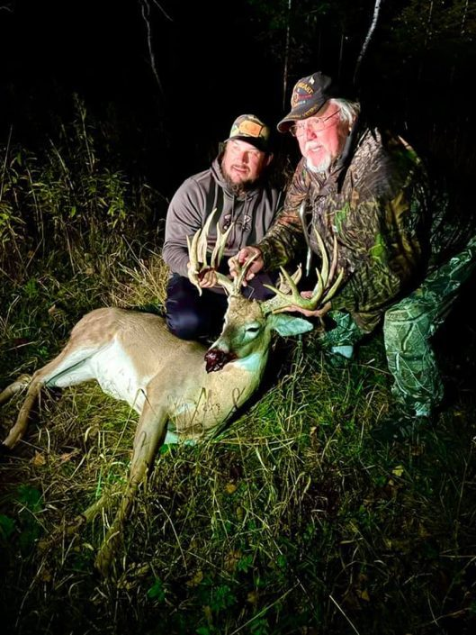 two men with buck shot at night