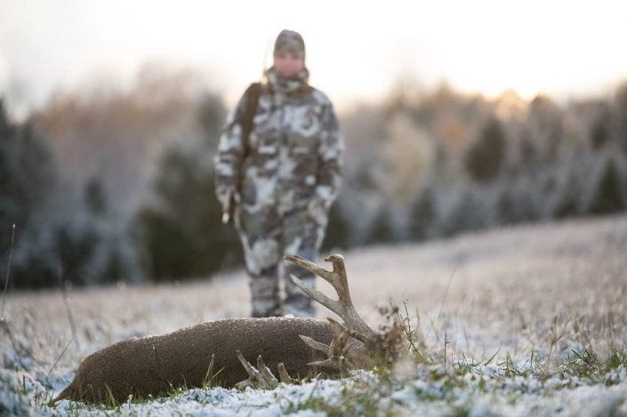 woman in the background of deer kill