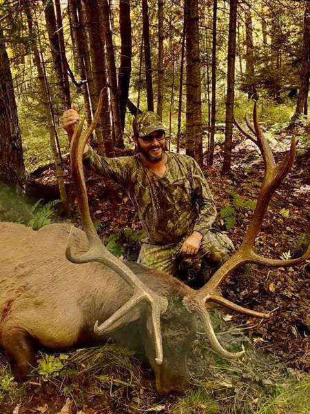 smiling man with deer kill
