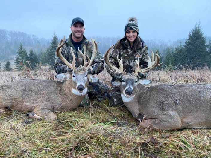 man and woman with deer kill