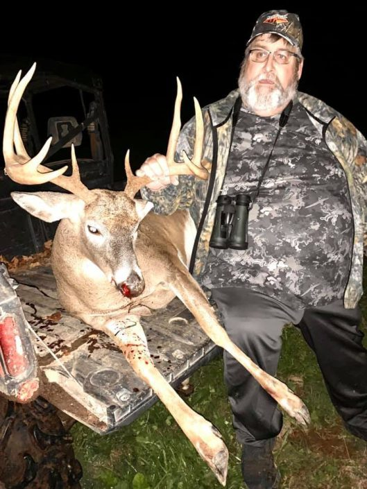 man posing with typical buck